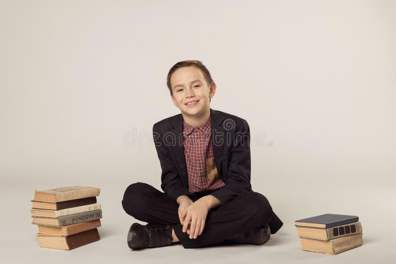 Muchacho lindo en un traje que se sienta en un fondo blanco Pila de libros fotos de archivo