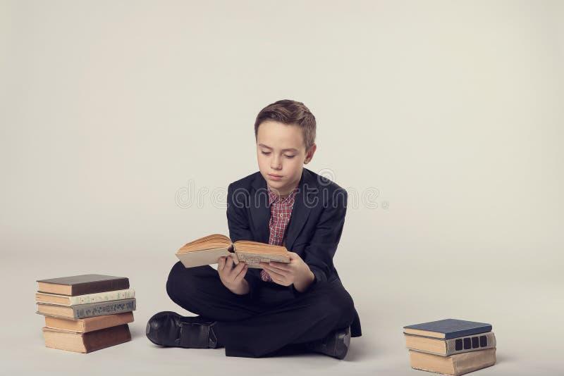 Muchacho lindo en un traje que sienta y que sostiene un libro en un fondo gris foto de archivo