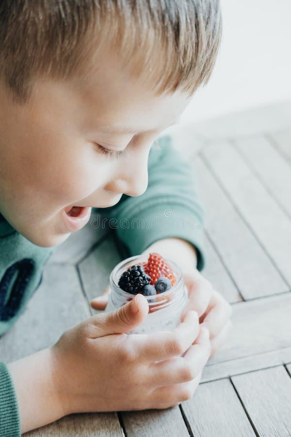 Muchacho lindo que come el pudín con las semillas del chia, el yogur y las frutas frescas foto de archivo