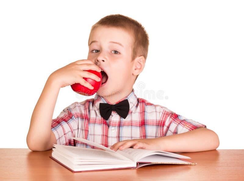 Muchacho lindo que come la manzana mientras que el sentarse en la tabla aisló fotografía de archivo