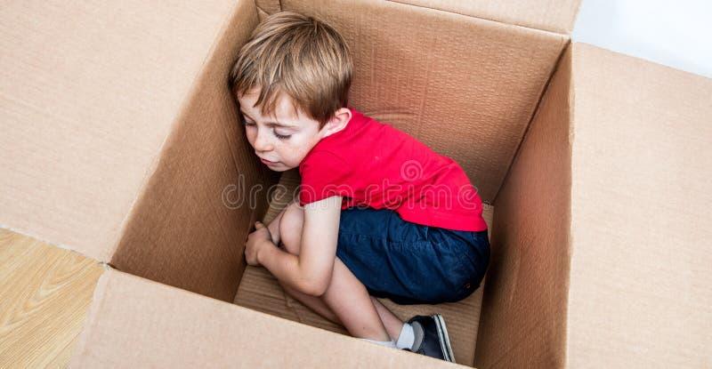 Muchacho lindo que duerme en una caja de cartón para el nuevo hogar fotografía de archivo