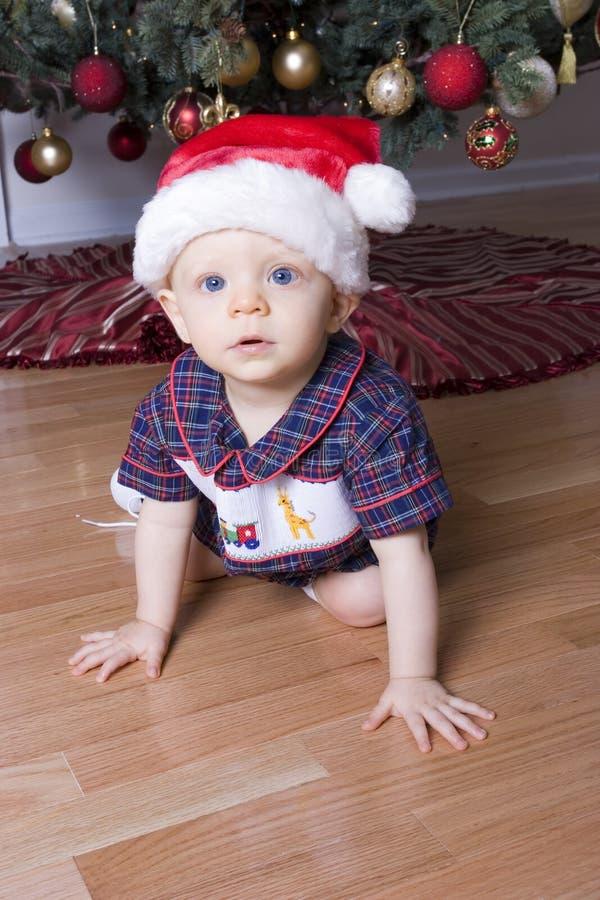 Muchacho lindo que juega bajo el árbol de navidad con el sombrero de santa fotografía de archivo libre de regalías