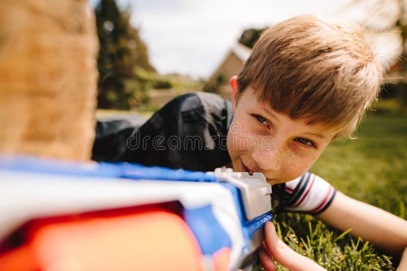 Muchacho lindo que juega con el arma del juguete en patio imagen de archivo