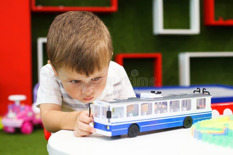 Muchacho lindo que juega con el coche de carretilla Juguetes que se convierten imagen de archivo libre de regalías