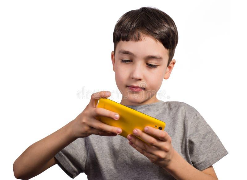 Muchacho lindo que juega con un smartphone fotografía de archivo