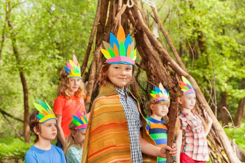 Muchacho lindo que lleva el traje del ` s de Injun cerca de su tienda india fotos de archivo libres de regalías