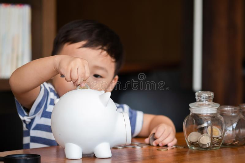 Muchacho lindo que pone monedas del dinero en la hucha, concepto de ahorro del dinero foto de archivo