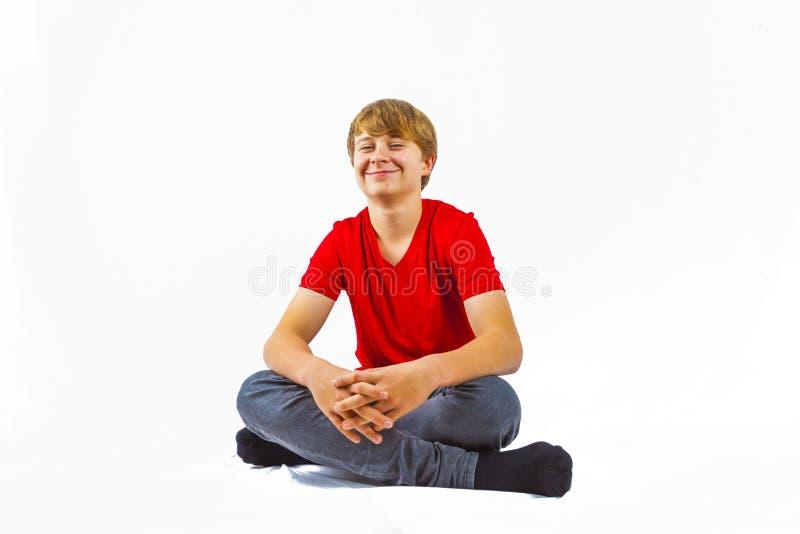 Muchacho lindo que se sienta en el piso foto de archivo