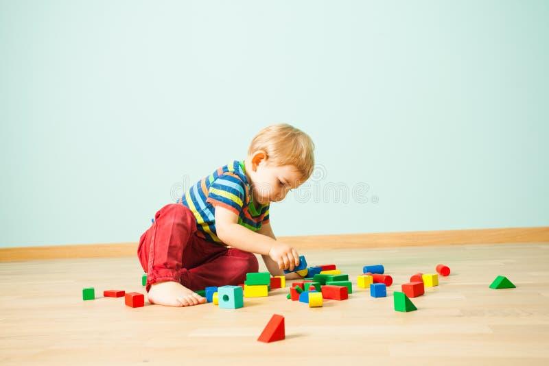 Muchacho lindo que se sienta en un piso que reconstruye torres rotas del juguete fotografía de archivo libre de regalías