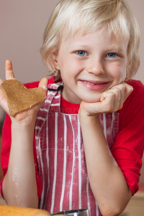 Muchacho lindo que soporta el corazón del amor del pan de jengibre fotografía de archivo