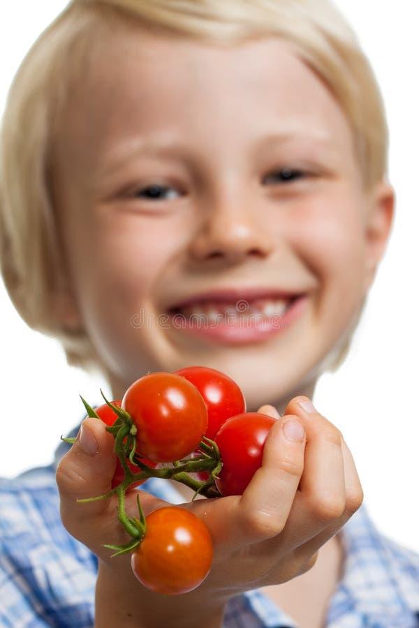 Muchacho lindo que sostiene hacia fuera el manojo de tomates foto de archivo