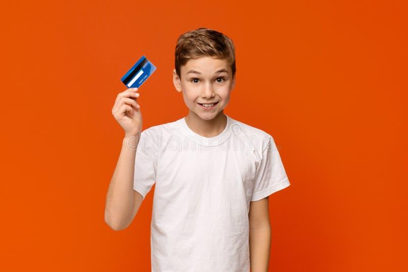 Muchacho lindo que sostiene la tarjeta de crédito, fondo anaranjado del estudio imagenes de archivo