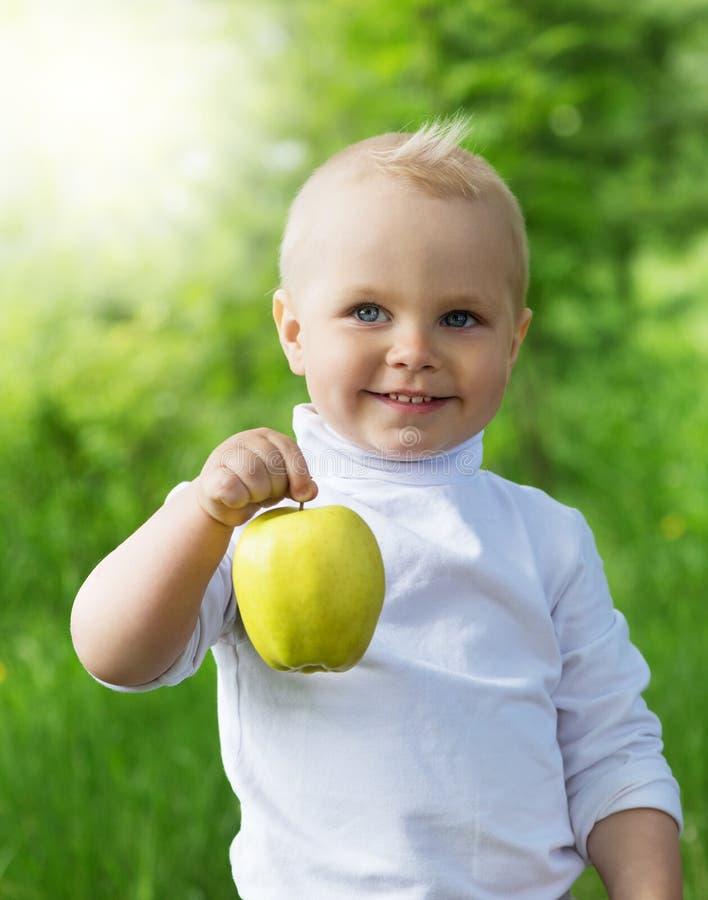 Muchacho lindo que sostiene una manzana imagenes de archivo