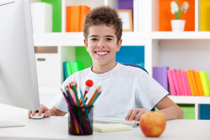 Muchacho lindo que usa un ordenador y una sonrisa imagenes de archivo