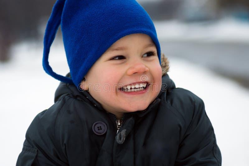 Muchacho lindo sonriente en el invierno imagenes de archivo