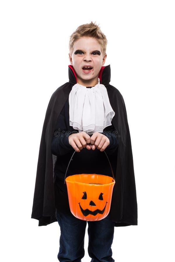Muchacho lindo vestido como vampiro para Halloween y sostener una cesta de la calabaza fotografía de archivo libre de regalías