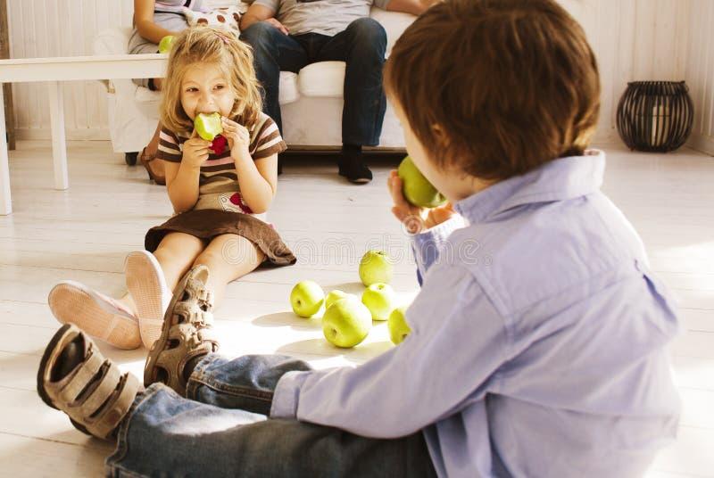 Muchacho lindo y muchacha que comen la manzana verde en casa imagen de archivo libre de regalías