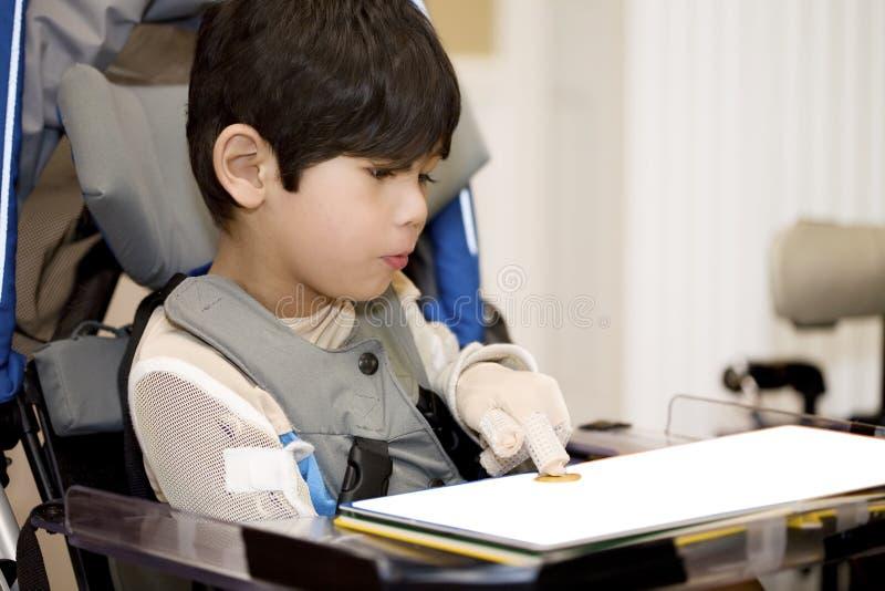 Muchacho lisiado joven que estudia en sillón de ruedas imágenes de archivo libres de regalías
