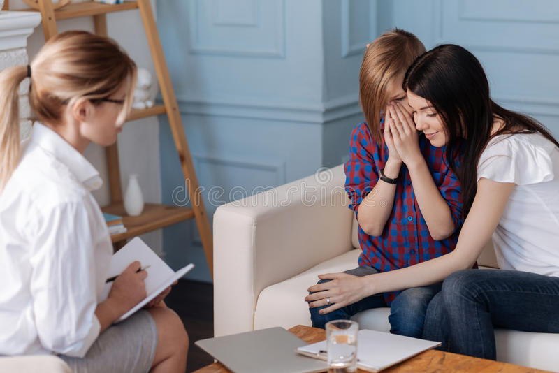 Muchacho lloroso que se sienta al lado de su madre foto de archivo libre de regalías