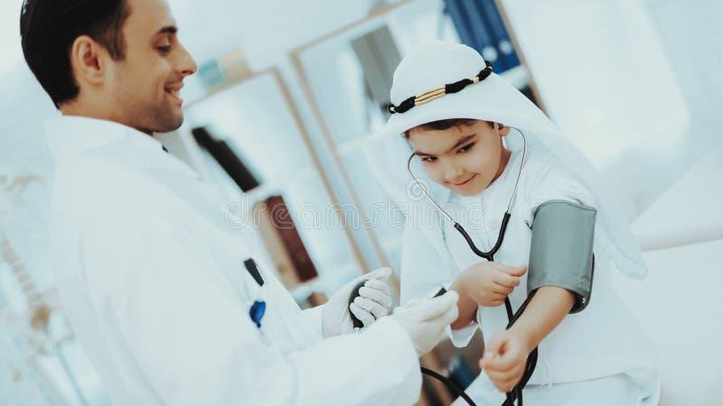 Muchacho masculino árabe del doctor Checking Blood Pressure fotos de archivo