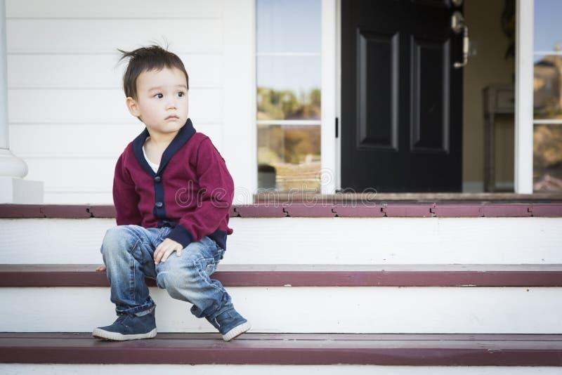 Muchacho melancólico de la raza mixta que se sienta en Front Porch Steps fotografía de archivo libre de regalías