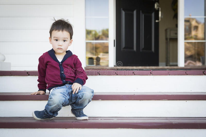 Muchacho melancólico de la raza mixta que se sienta en Front Porch Steps imágenes de archivo libres de regalías