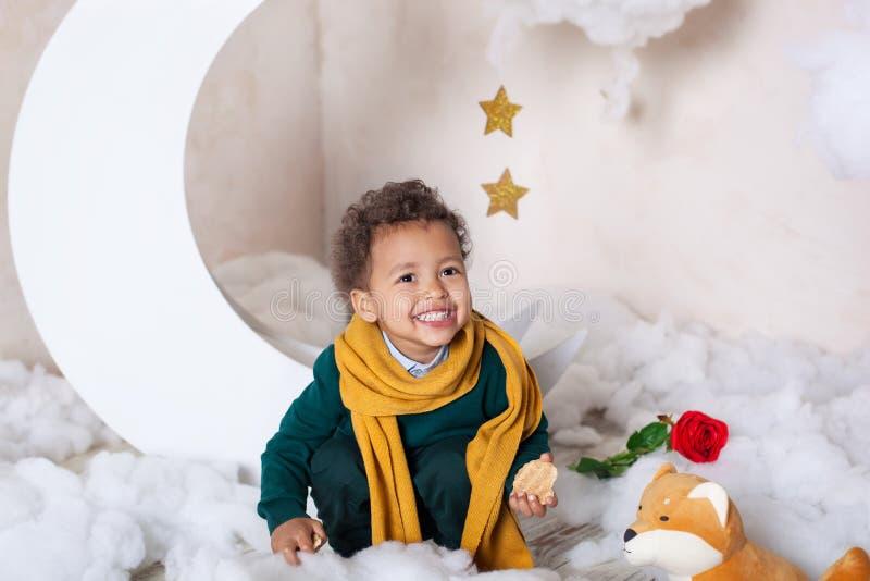 Muchacho negro en un suéter verde y una sonrisa amarilla de la bufanda Peque?o pr?ncipe El ni?o come las galletas escandinavia El imágenes de archivo libres de regalías
