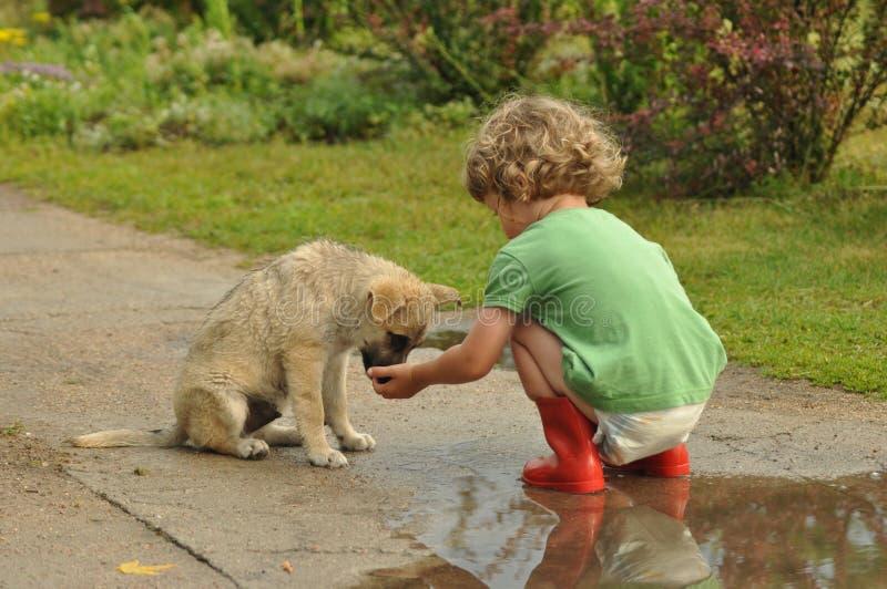 Muchacho, niño en Wellingtons de goma rojo que habla con el perrito Niñez en pañales imagenes de archivo