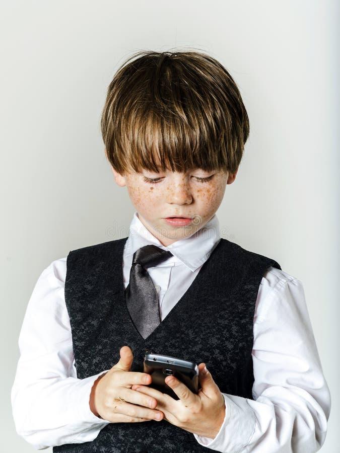 Muchacho pelirrojo emocional con el teléfono móvil fotografía de archivo libre de regalías