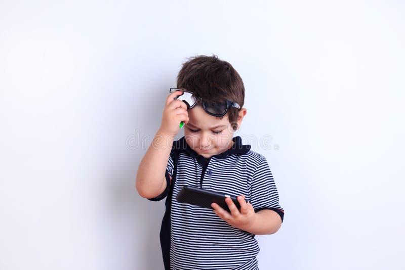 Muchacho pensativo en gafas de sol con smartphone Niño que aprende cómo a imagenes de archivo