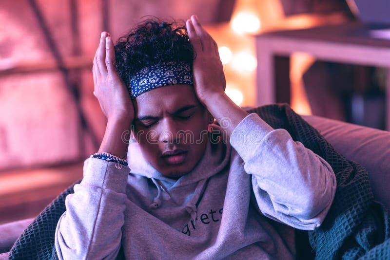 Muchacho pobre que tiene una recaída de un dolor de cabeza severo del cual él sufre fotografía de archivo