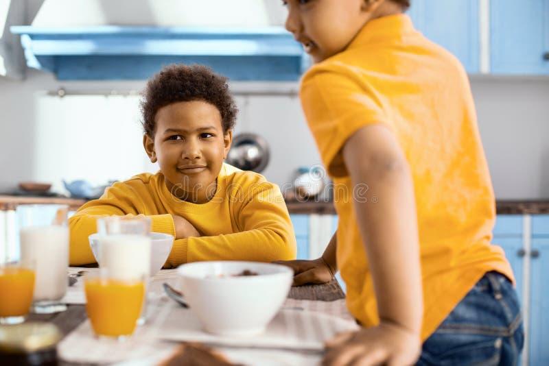Muchacho pre-adolescente agradable que desayuna con su hermano foto de archivo
