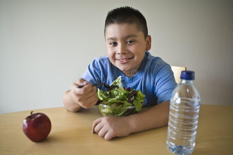 Muchacho preadolescente feliz que come la ensalada foto de archivo libre de regalías