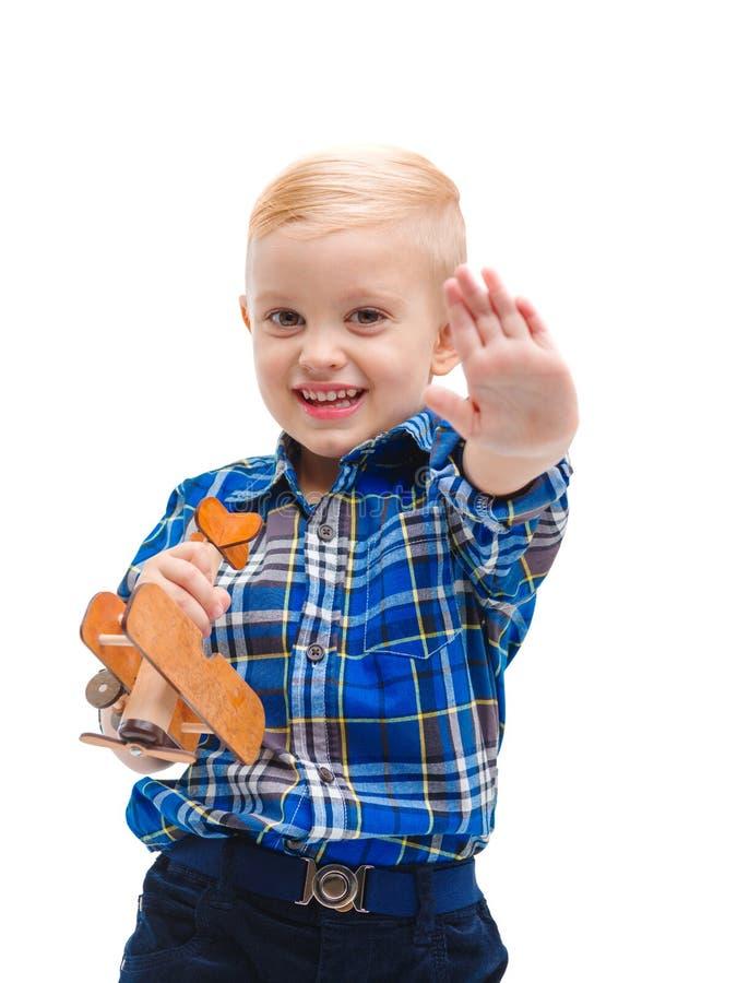 Muchacho precioso del niño, agitando su mano y sosteniendo un aeroplano del juguete en sus manos Aislado en blanco imagen de archivo libre de regalías