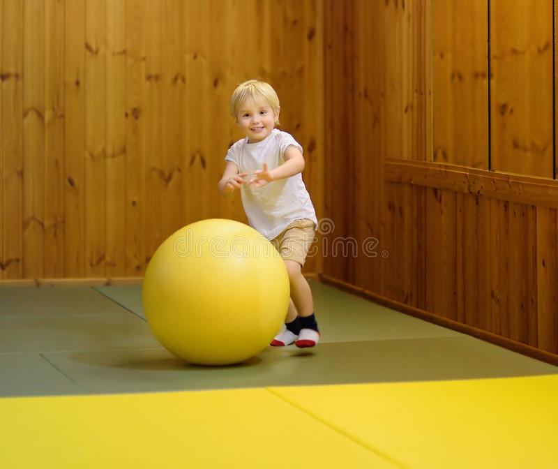 Muchacho preescolar activo que juega con la bola grande en pasillo de deportes interiores/clase del gimnasio fotografía de archivo libre de regalías
