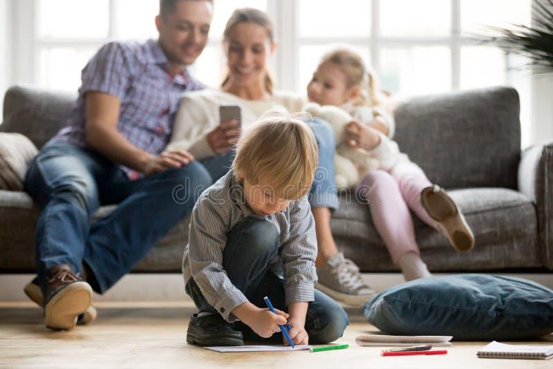 Muchacho preescolar del niño que sostiene el dibujo del marcador del color que juega en casa imagen de archivo libre de regalías