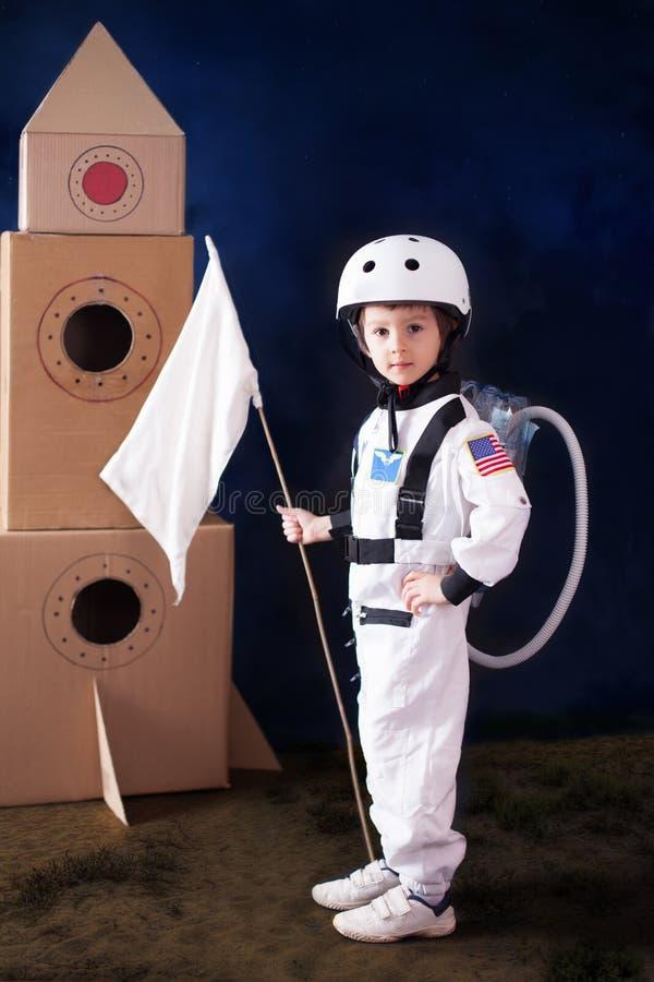 Muchacho preescolar hermoso, vestido como astronauta, con la bandera y el coche fotos de archivo libres de regalías