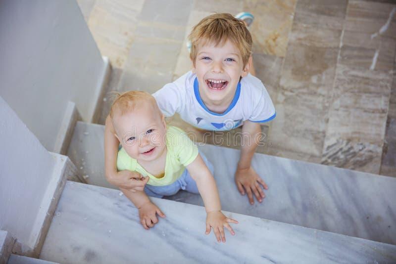 Muchacho preescolar y bebé que miran para arriba la cámara y que sonríen al aire libre imagen de archivo
