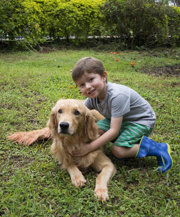Muchacho que abraza el perro imagen de archivo libre de regalías