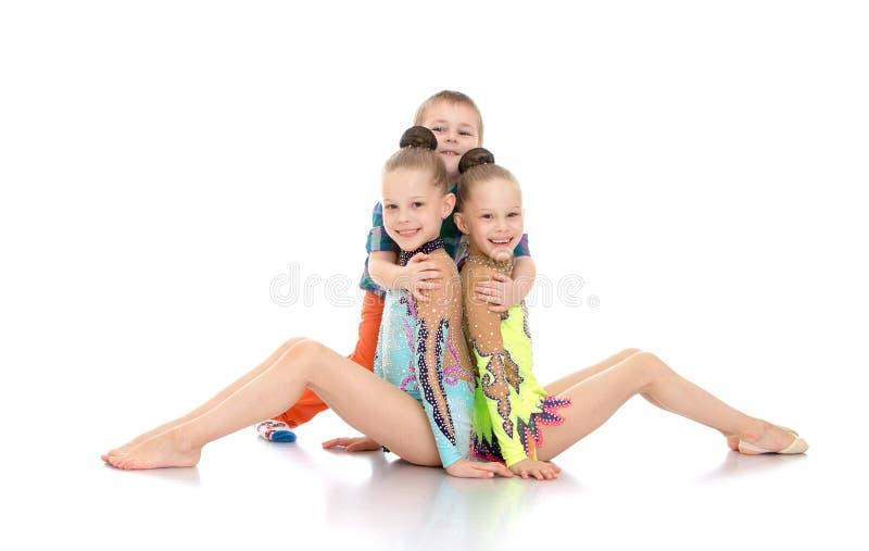 Muchacho que abraza a gimnastas de las muchachas fotografía de archivo libre de regalías
