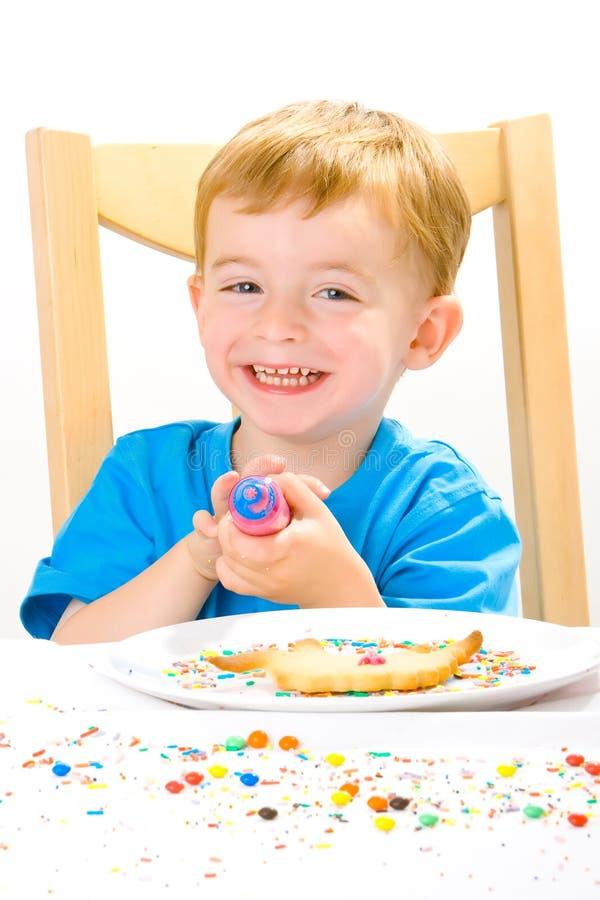 Muchacho que adorna las galletas cocidas al horno fotos de archivo