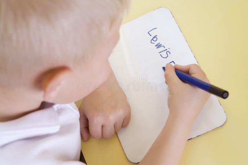 Muchacho que aprende escribir nombre en clase primaria fotos de archivo