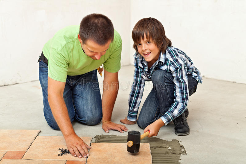 Muchacho que ayuda a su padre que coloca una baldosa de cerámica imagen de archivo
