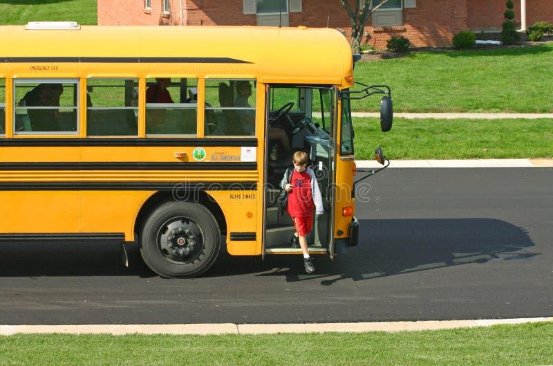 Muchacho que baja del autobús escolar foto de archivo