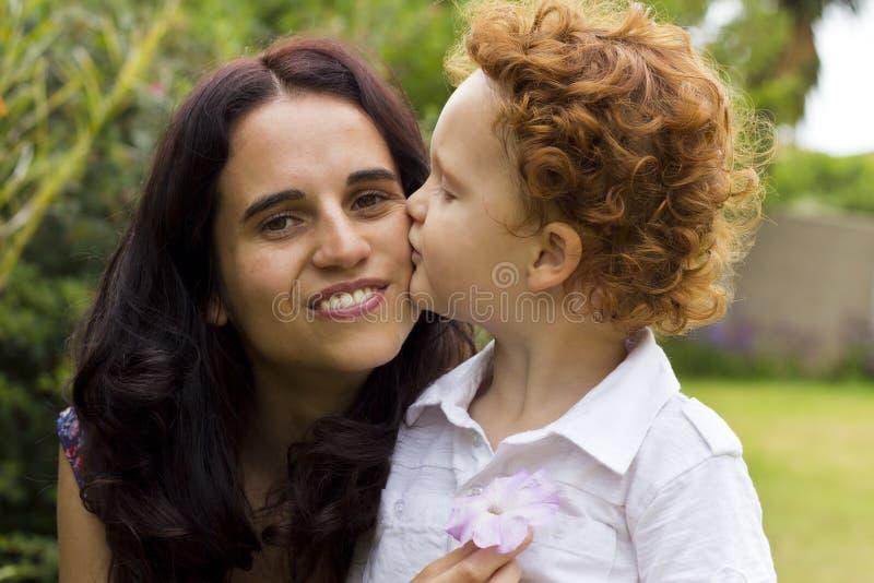 Muchacho que besa a la madre en su mejilla foto de archivo libre de regalías