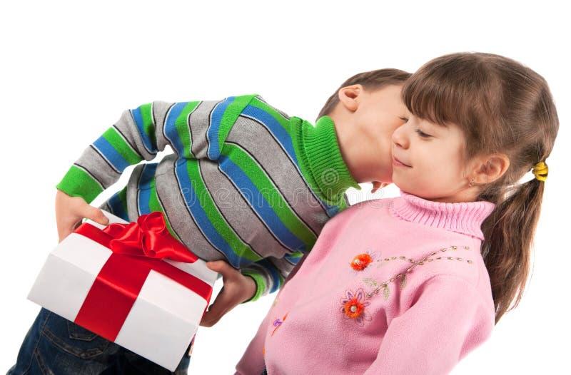 Muchacho que besa un rectángulo de regalo de la explotación agrícola de la muchacha imagen de archivo libre de regalías