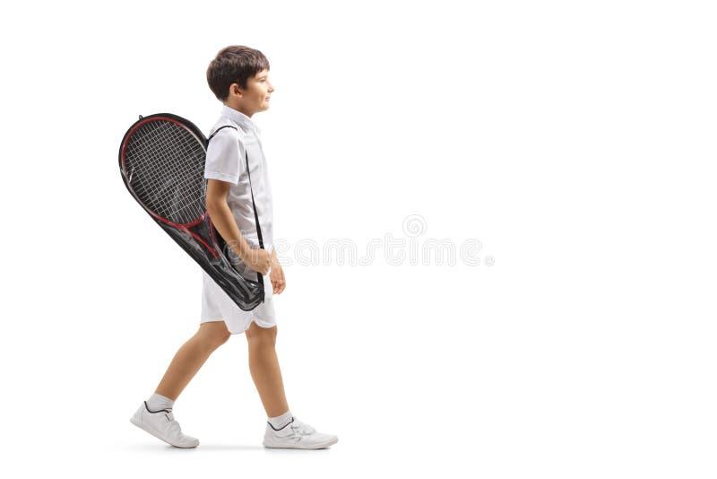 Muchacho que camina con una estafa de tenis en un caso fotos de archivo