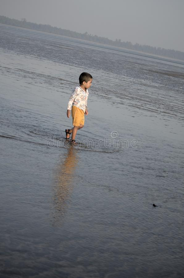 Muchacho que camina en agua de mar imagen de archivo