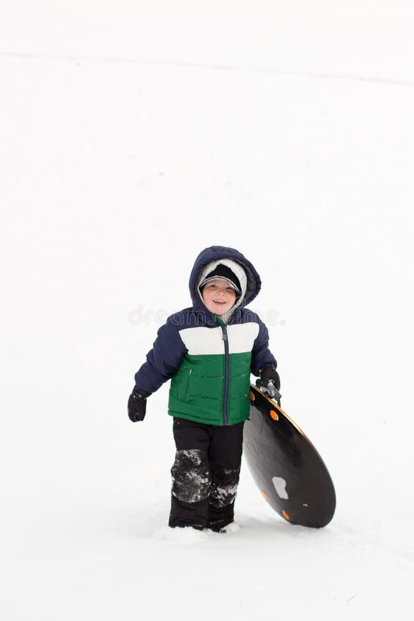 Muchacho que camina encima de una colina sledding con el wint de la nieve del trineo fotografía de archivo libre de regalías