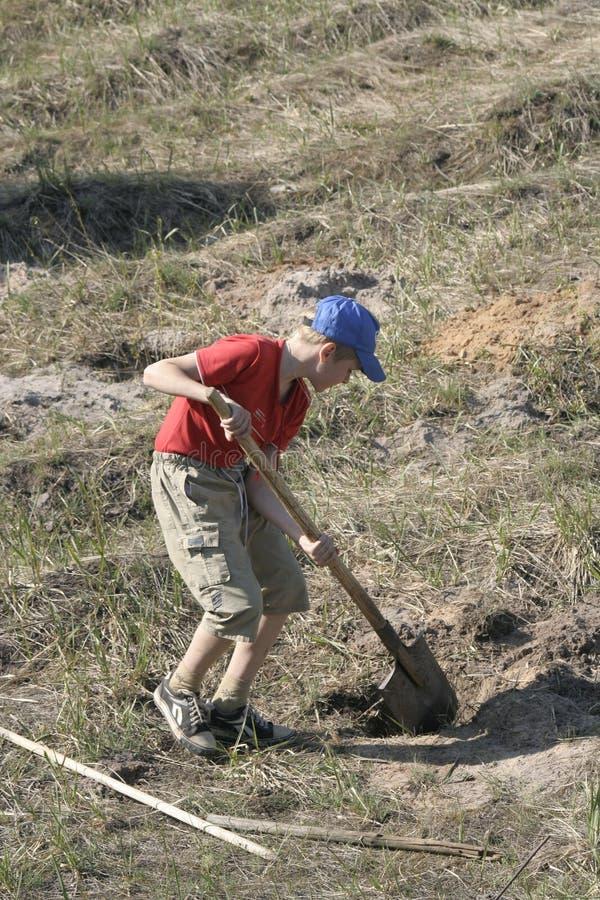 Muchacho que cava en campo foto de archivo libre de regalías